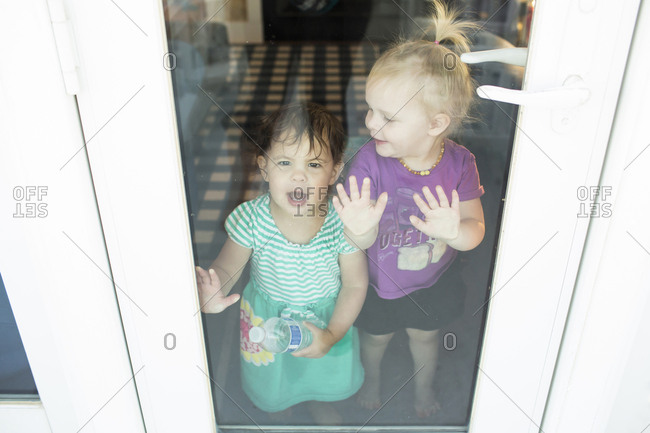 Sisters standing by door seen through glass