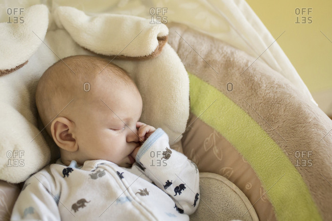 High angle view of baby boy sucking thumb while sleeping in bassinet