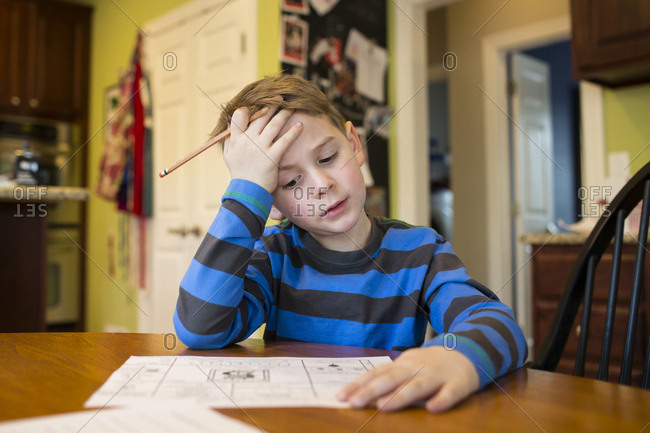 Boy studying by table at home
