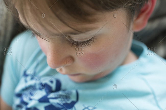 Close-up of boy sitting at home