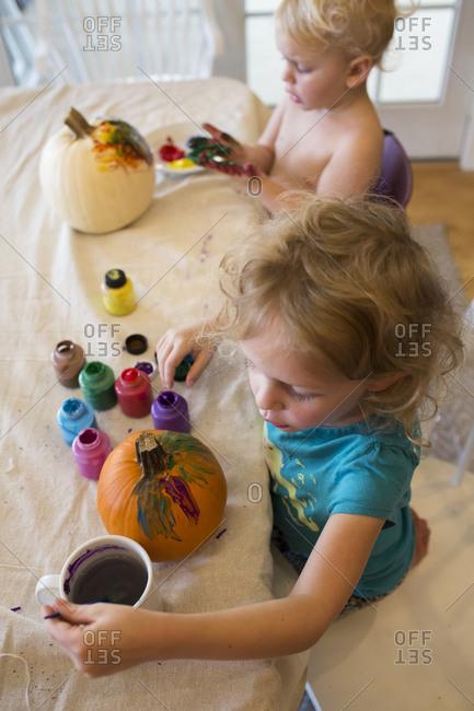 High angle view of siblings painting pumpkins at home