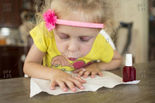 Girl painting fingernails at home