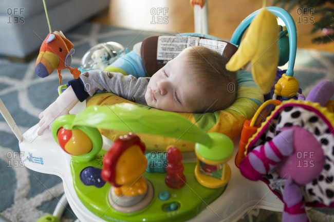 High angle view of baby boy sleeping in walker at home