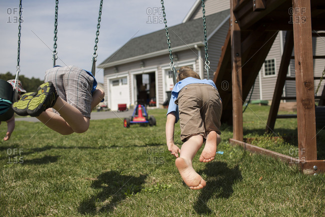 Brothers swinging in backyard during sunny day