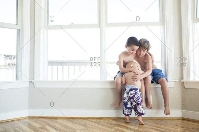 Shirtless brothers embracing by window at home