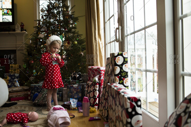 Girl standing by Christmas tree at home