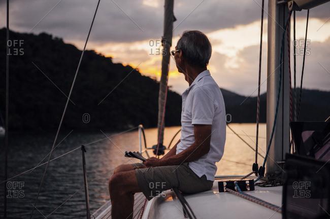 Senior man looking away while traveling sailboat on sea