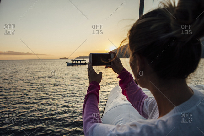 Woman photographing while traveling in sailboat on sea during sunset