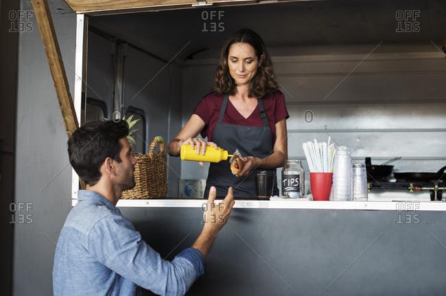 Owner serving hotdog for customer at food truck
