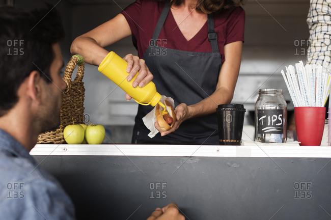 Midsection of female vendor serving hotdog for customer at food truck