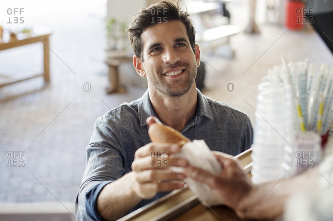 Customer receiving hotdog from male vendor at food truck