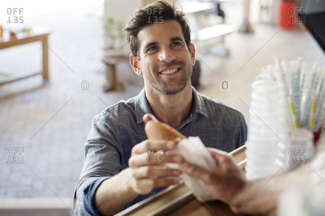 Customer receiving hotdog from male vendor at food truck
