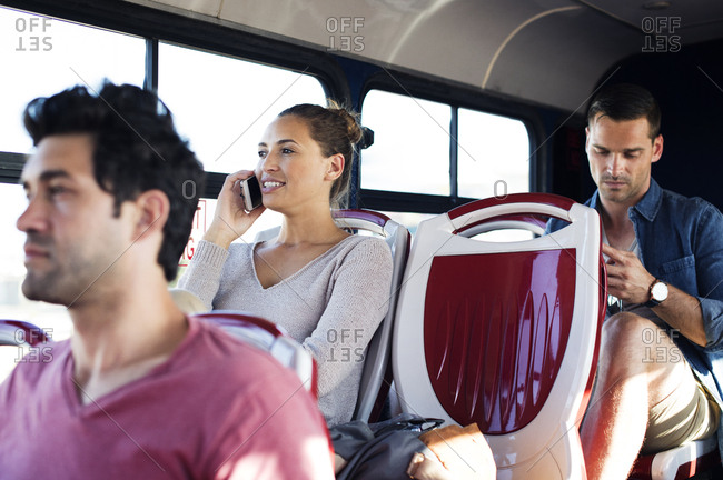 Woman talking on mobile phone while traveling with other passengers in tour bus