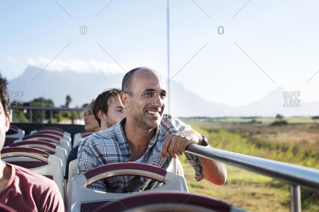 Tourists looking at view while traveling in double-decker bus against sky