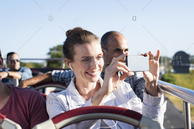 Woman photographing while traveling in double-decker bus