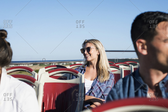 Tourists traveling in double-decker bus against clear blue sky