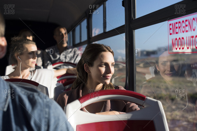 Passengers looking through window while traveling in tour bus