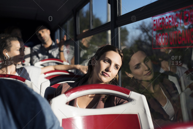 Tourists looking through window while traveling in bus