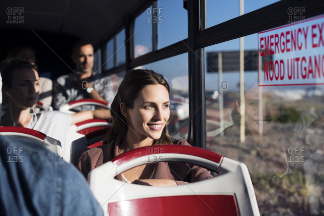 Tourists looking through window while traveling in tour bus
