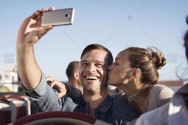 Happy man taking selfie while girlfriend kissing him in double-decker bus