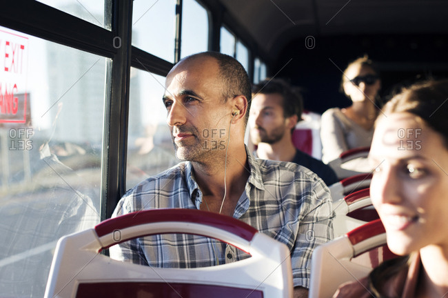 Passengers looking through window while traveling in bus
