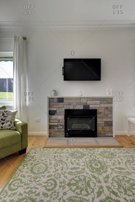 Television set on wall above fireplace in modern living room