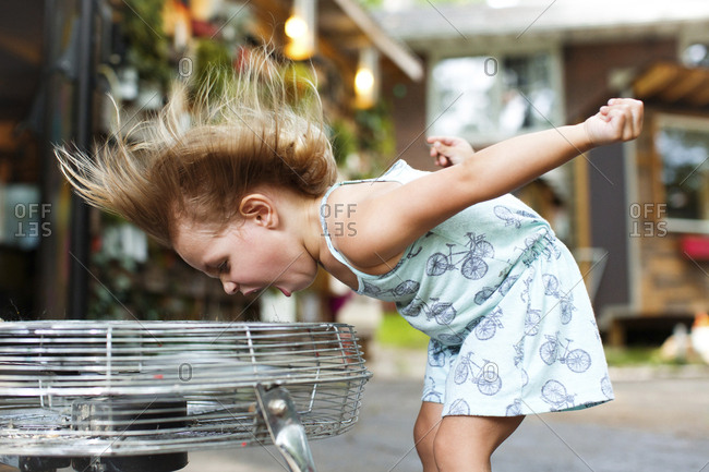Girl screaming while enjoying breeze from electric fan