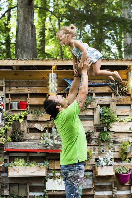 Playful father throwing daughter in air while standing at backyard