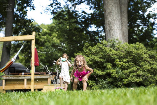 Girl photographing while sister playing with sprinkler in backyard