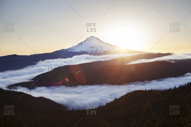 Scenic view of mountain covered with clouds during sunrise