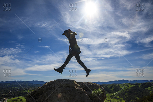 Side view of man jumping on rock formations against sky during sunny day