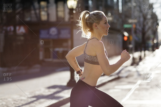 Side view of female athlete running on city street during sunny day