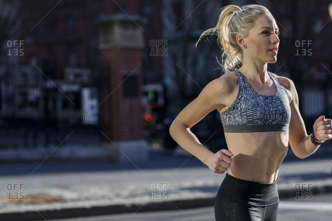 Female athlete running on street during sunny day