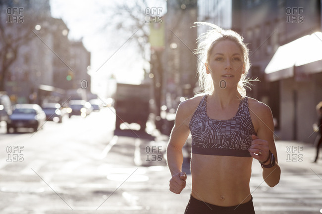 Confident female athlete running on city street during sunny day