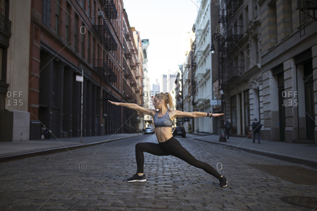 Female athlete exercising on street in city