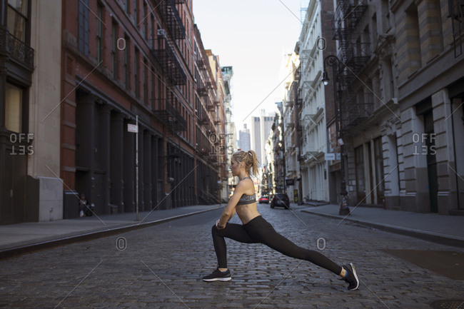 Side view of woman exercising on street in city