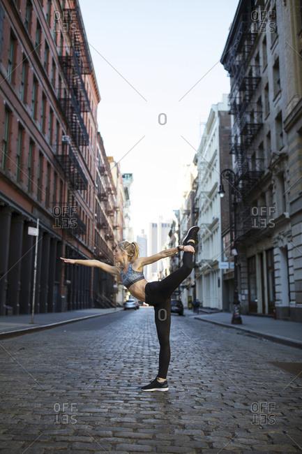 Female athlete exercising on street against sky in city