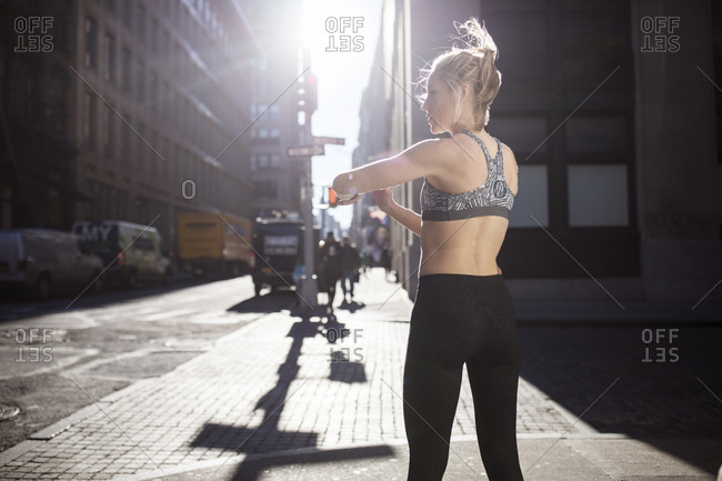 Rear view of female athlete standing on city street during sunny day