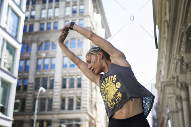 Low angle view of female athlete stretching hands on city street