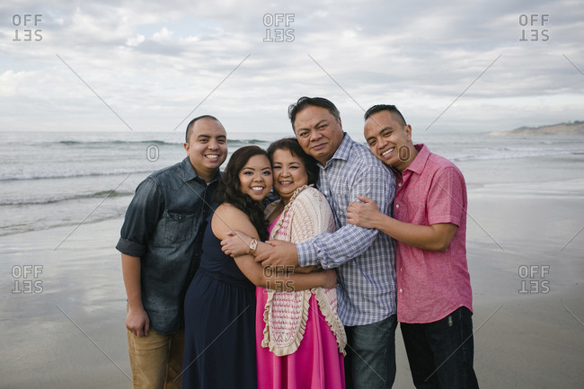 Portrait of happy family standing on shore at beach against sky
