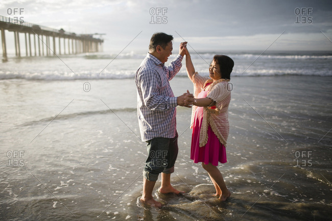 Side view of couple dancing on shore at beach