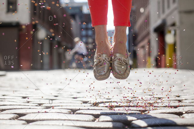 Low section of woman with confetti jumping on cobble street during sunny day