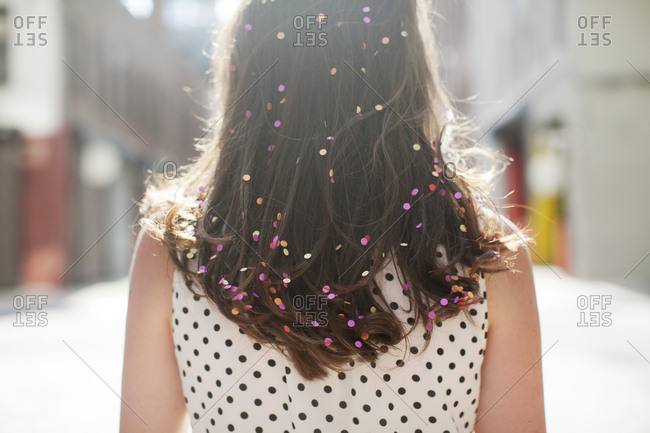 Rear view of woman with confetti on hair during sunny day