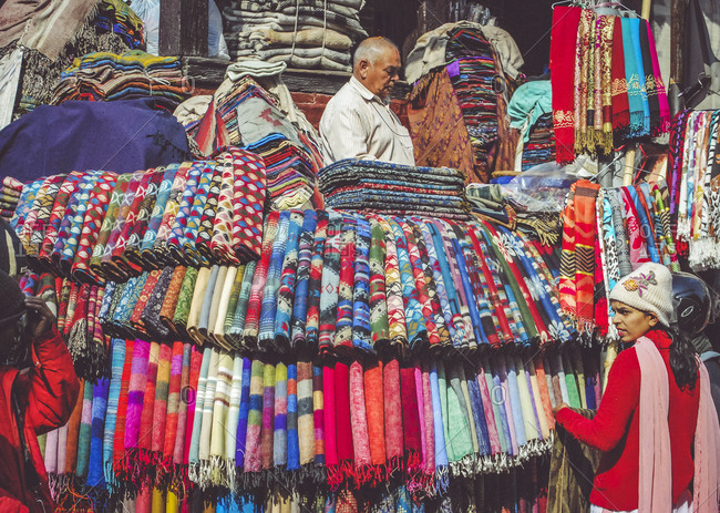 Nepal, Kathmandu - January 23, 2012: People standing by shawls for sale at market