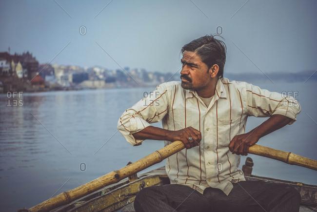 India, Varanasi - January 28, 2012: Man oaring in river
