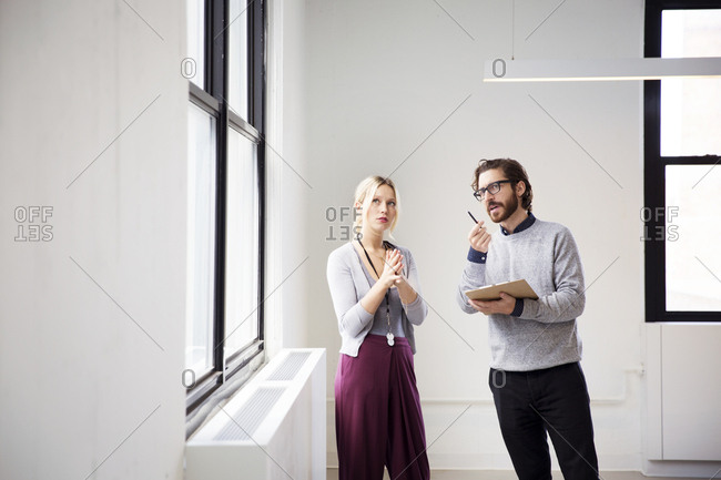 Real estate agent explaining new office area to businesswoman