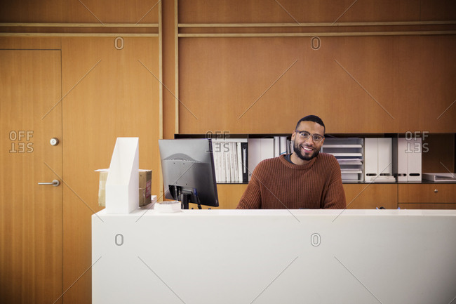 Portrait of smiling businessman sitting by desktop computer in office