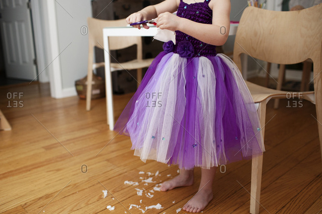 Low section of girl cutting paper while standing on hardwood floor at home