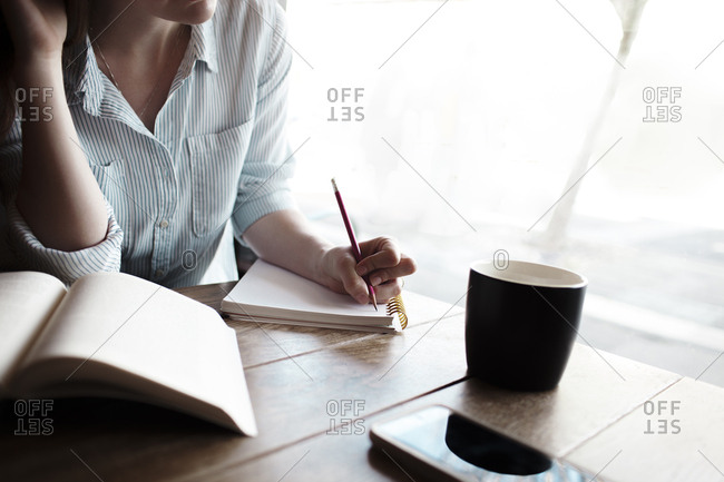 Midsection of woman writing notes in cafe