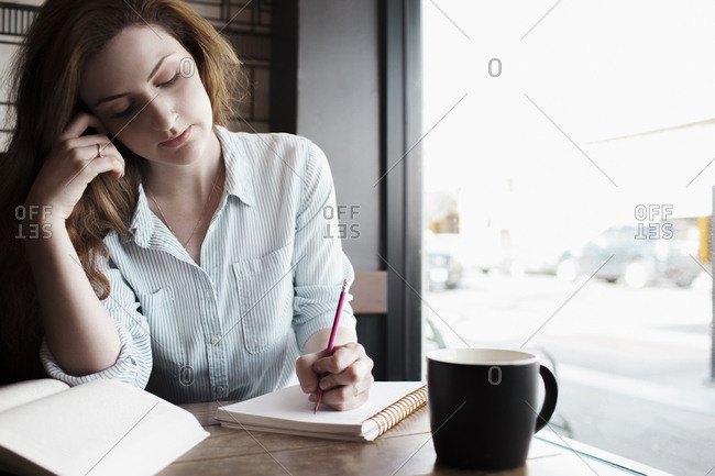 Woman studying while sitting by window in cafe